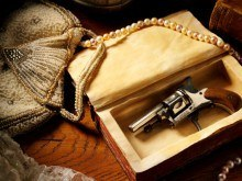 Mystery and Crime - a gun in a antique jewellery box with pearls, perfume and a book.